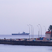 As fishermen and  try their luck on the Malecon, a Cuban Navy vessel patrols the coast. Fishing is not only a favorite pastime for Cubans but it is also an income source.<br />   Photography by Jose More