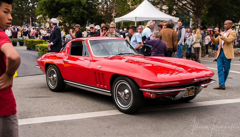 A red classic 1965 Corvette Stingray in motion at the 2017 Carmel-by-the-Sea Concours on the Avenue