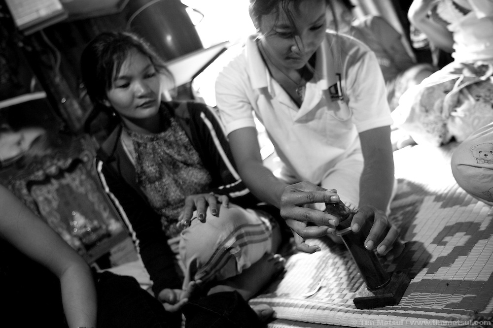 "Srey Kah, a prostitute living in a slum where ""Acting for Women in Distressing Situations"" (AFESIP) conducts outreach and provides services, practices condom application during an AFESIP talk in Phnom Penh, Cambodia. Srey Kah was raped at 16 in her home town, later she was sold by a friend and held captive as a sex worker, then arrived in Phnom Penh and turned to prostitution to survive; she has survived beatings, gang rapes, drugs, and self mutilation. She continues as a prostitute so she can support her mother and put her younger sister through public school. Srey Kah's story is not unique. The slum's permanent structure, a decaying four story building known simply as 'The Building', was built in the 1960's as transitional housing and now hosts a shantytown where many of the city's poor live, including many prostitutes, and is believed to have the highest rate of HIV infection in the city. AFESIP hands out free condoms, instructs prostitutes on HIV prevention, and conducts outreach in case the prostitutes need medical services, choose to leave their profession, or can report on cases of sex trafficking. AFESIP offers housing, education, training, and counseling for women who are victims of sex trafficking, worked as prostitutes, or are escaping domestic violence. Founded by Somaly Mam, who herself was once a prostitute and victim of trafficking and domestic abuse, AFESIP has three facilities in Cambodia and works with other NGO's to provide long term care for the women."