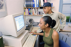 Teenage girl and boy using computer at home,