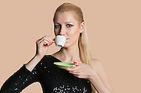 Portrait of beautiful young woman drinking tea over colored background