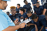 """While the other players eat oranges and drink water in the shade during halftime, Maxwell """"Bunchie"""" Young, 10, stands glued to the hip of coach Juan Harmon as he draws up a few new offensive routes for Bunchie to run in the second half."""