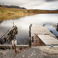 A long exposure of a dock on a lake in the hills of the northern part of County Galway in Ireland.