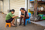 14 MARCH 2013 - BOTEN, LAOS:  Shopkeepers in the Chinese market in Boten, Laos, wait for customers. There is a large Chinese emigrant community in the Boten Special Economic Zone in northern Laos. The Chinese market in Boten is virtually empty because the goods sold in the market are too expensive for the Lao to purchase. PHOTO BY JACK KURTZ
