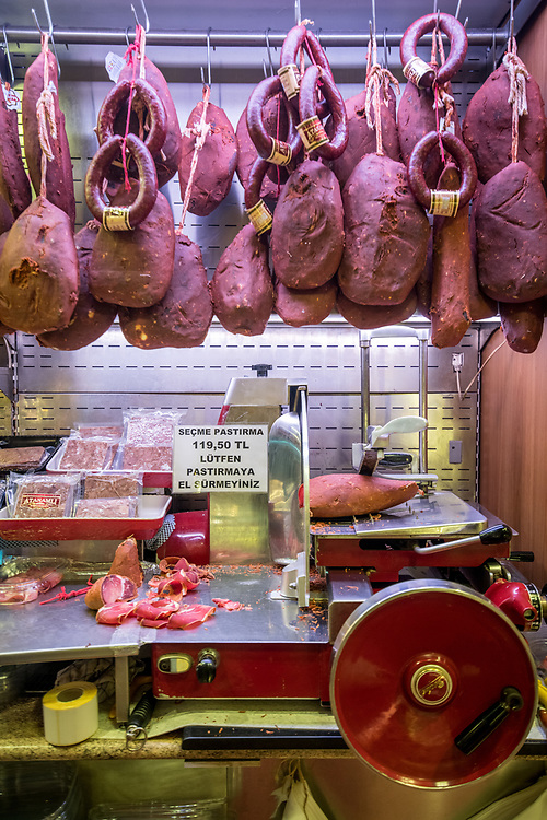 A selection of cured meats hang on display for sale in butcher shop at Istanbul Spice bazaar in Turkey