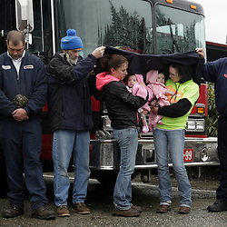 "Klarissa Calviste (3rd L), holding daughter Kielie Braaten, and Brooke Odenius (2nd L), holding daughter Bexli Odenius, get help staying dry as workers and community members observe the one-week anniversary of the Oso landslide with a prayer and moment of silence at fire station in Darrington, Washington March 29, 2014. Family and friends of 90 people still missing after a wall of mud flattened the outskirts of a rural Washington state town increasingly feared for the worst on Saturday as the governor called for a statewide moment of silence a week after the disaster. ""The number is so big and it's so negative. It's hard to grasp,"" said 66-year-old Bob Michajla, a volunteer who has been helping search part of the square-mile (2.6 square-km) debris field. ""These are all friends and neighbors and family. Everybody knows everybody in this valley.""  REUTERS/Jason Redmond (UNITED STATES)"