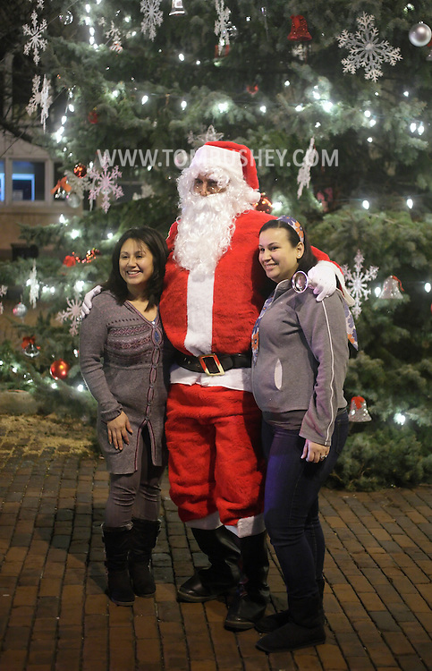 Newburgh, New York- Two women pose for a picture with Santa Claus after the Christmas tree lighting ceremony on Broadway on the night of Dec. 14, 2011.