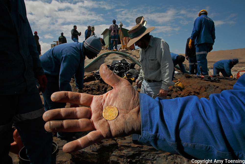 ORANJEMUND, NAMIBIA -- SEPTEMBER 30: Namdeb mine worker holds one of the 3 Excellentes coins, which display inscriptions of King Ferdinand and Queen Isabella, known for uniting Spain in the early 1500s found on September 30, 2008 in Oranjemund, Namibia. The wreck was uncovered by miners in the Namdeb diamond mine off the coast of Namibia. The ship was found seven meters below sea level on April 1, 2008. Archeologists presume the wreck is from the early 1500s. Most of the the artifacts found are being stored in a storage shed at the Namdeb Diamond Mine. Items include: copper ingots, bronze canons, canon balls, pewter bowls and plates, ivory tusks from African elephants, and most substantial over 2000 gold coins - approximately 21 kg - the most gold found in Africa since the Valley of the Kings in Egypt. (Photo by Amy Toensing) _________________________________<br />