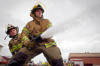 JEROME A. POLLOS/Press..Kootenai County firefighter Adam Godwin operates a nozzle while learning how to properly spray foam Tuesday in Post Falls as he is backed up by fellow firefighter Rex Nielsen.