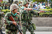 14 MAY 2010 - BANGKOK, THAILAND: Thai troops advance down Rama IV Road in Bangkok Friday firing shotguns at protesters. Thai troops and anti government protesters clashed on Rama IV Road Friday afternoon in a series of running battles. Troops fired into the air and at protesters after protesters attacked the troops with rocket and small homemade explosives. Unlike similar confrontations in Bangkok, these protesters were not Red Shirts. Most of the protesters were residents of nearby Khlong Toei slum area, Bangkok's largest slum area. The running battle went on for at least two hours.   PHOTO BY JACK KURTZ