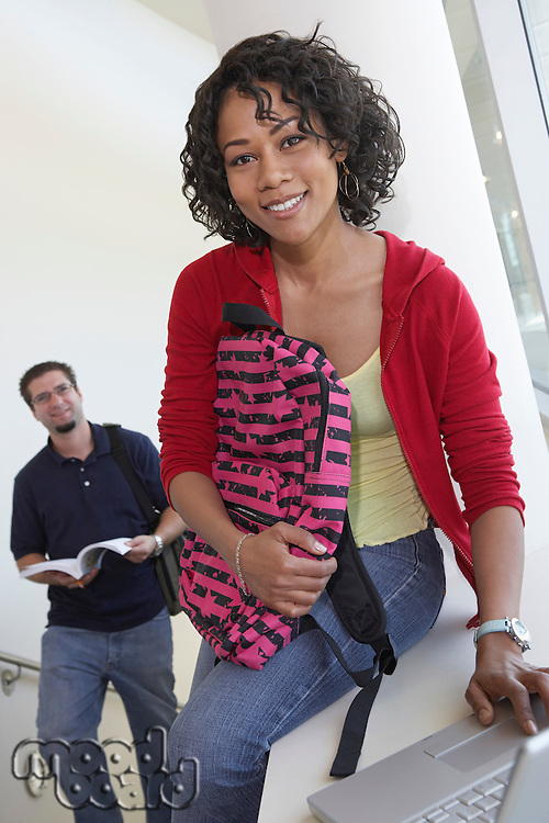 Portrait of female student using laptop on stairs, man in background