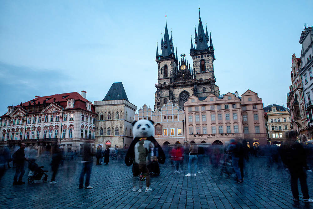 """A street perfomer dressed as a panda in-front of a crowd at Old Town Square. The """"Church of Our Lady before Týn"""" in the back."""