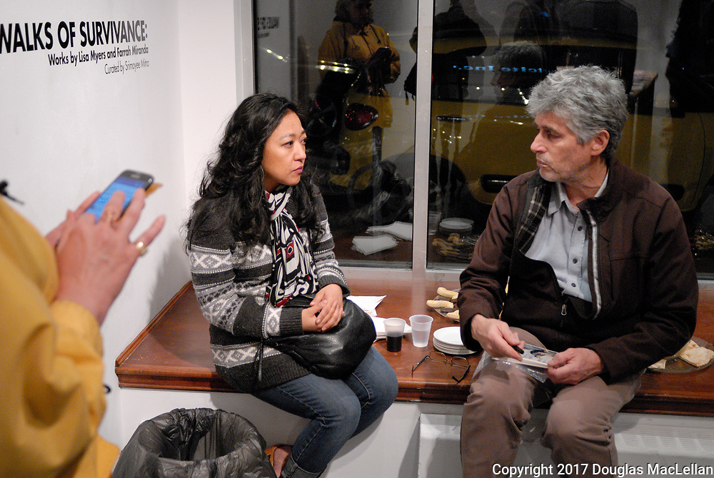 """CANADA, Windsor. May 2017. Opening Reception of """"Walks of Survivance: Works by Lisa Myers and Farrah Miranda"""", currated by Srimoyee Chitra. """"Walks"""" is part of MayWorks Windsor 2017 programming. Leaft to right: Mireille Coral on smartphone, Elizabeth, a union organizer and Paul Chislett, president of Windsor Workers Education Centre."""