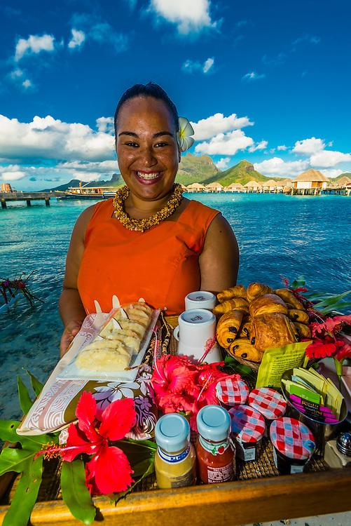 A Polynesian woman serving a breakfast tray with croissant and pain au chocolat, Four Seasons Resort Bora Bora, French Polynesia.