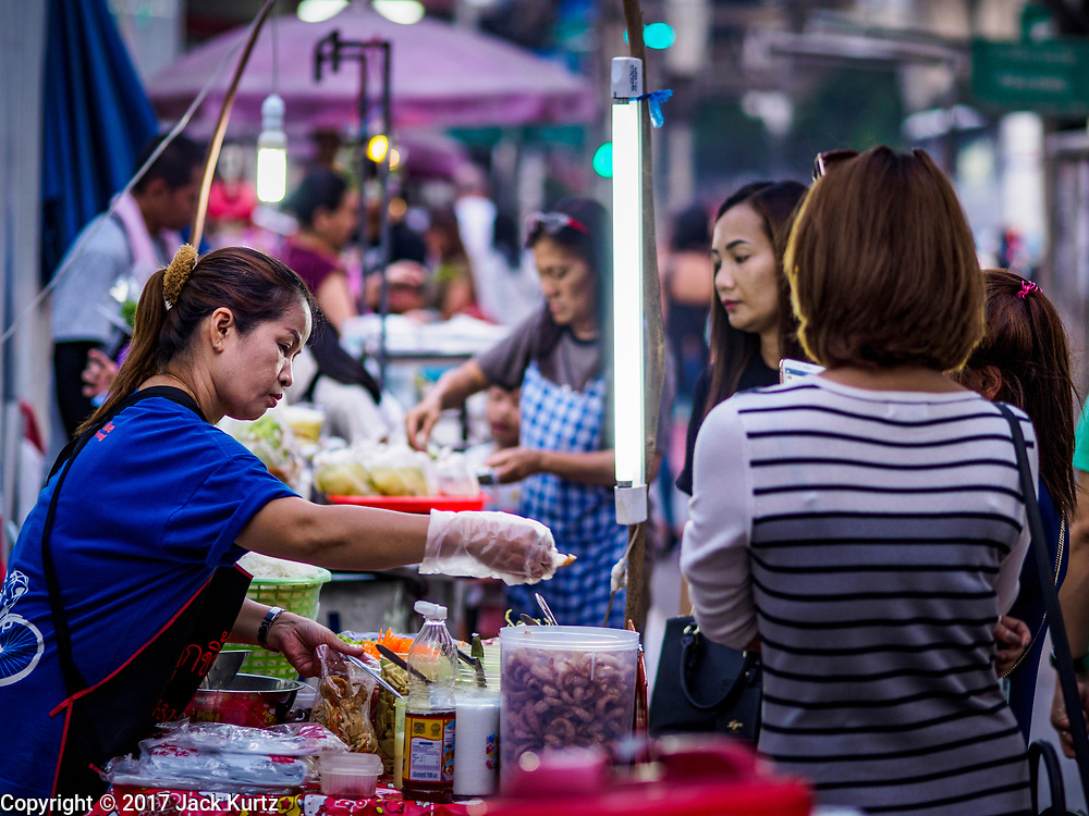 24 MARCH 2017 - BANGKOK, THAILAND: A street food vendor makes a salad on Sukhumvit Road near Soi 69 (Phra Khanong). The coconut water vendor and the food carts behind her have to leave the area by 17 April. Food cart vendors along Sukhumvit Road between Sois 55 (Thong Lo) and 69 (Phra Khanong) in Bangkok have been told by city officials that they have to leave the area by 17 April. It's a part of an effort by Bangkok city government, supported by the ruling junta, to take back the city's sidewalks. The evictions in the area are the latest in mass evictions of Bangkok street food vendors after similar actions elsewhere on Sukhumvit, in the Ari area, in Silom/Patpong and Ratchaprasong neighborhoods. The vendors in Thong Lo/Phra Khanong are popular with local office workers because most of the formal restaurants in the area serve foreign tourists and upper class Thais and are very expensive. The street food carts serve meals starting at about 35Baht ($1US). The city has not announced if they will provide alternative locations for the carts.     PHOTO BY JACK KURTZ