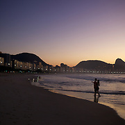 A couple enjoy a tender moment as they witness the amazing sunrise at Rio de Janeiro's most famous beach Copacabana with Sugar Loaf mountain in the distance. Rio de Janeiro, Brazil. 21st July 2010. Photo Tim Clayton..