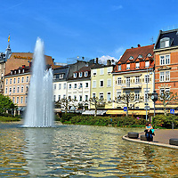Augustaplatz Square and Fountain in Baden-Baden, Germany<br /> Augustaplatz is a lovely square located along Lichtentaler Straße, a main street running through the center of Baden-Baden, Germany. The picturesque plaza offers a tranquil place to sit beside a fountain for a few minutes when you get tired during your walking tour. A short distance away are most of the spa town's landmarks.