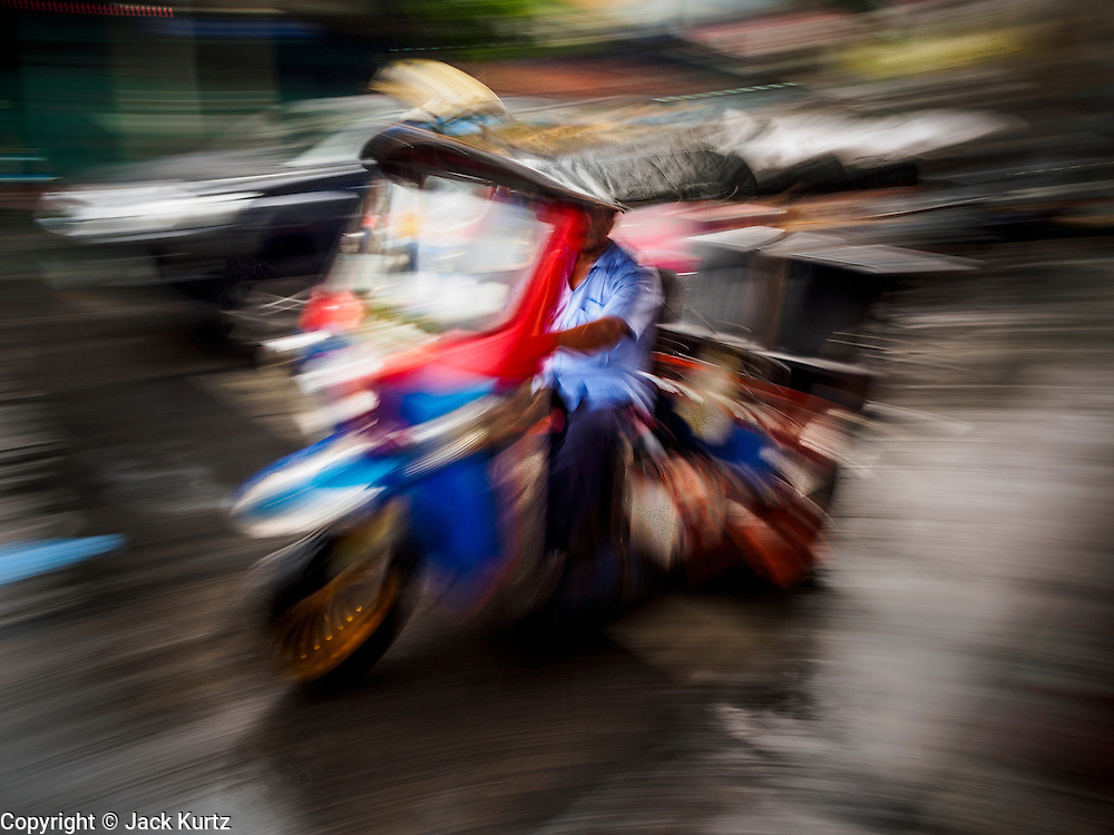 24 MARCH 2014 - BANGKOK, THAILAND:  A tuk-tuk, or three wheeled taxi, on a street in Bangkok's Chinatown district. Tuk-tuks are a common form of transportation in Asia.    PHOTO BY JACK KURTZ
