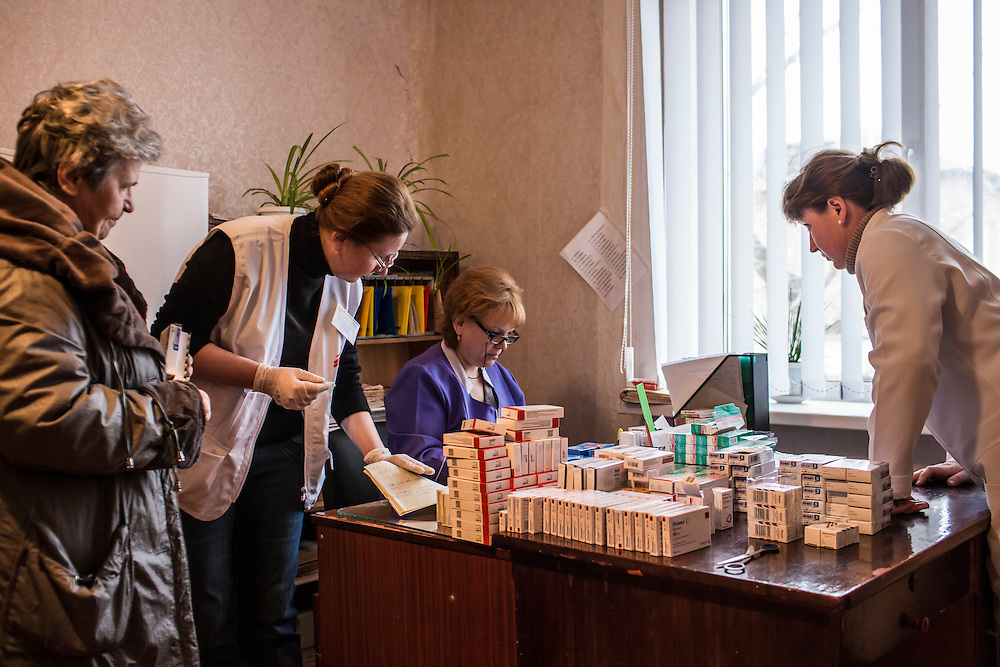 ZIMOGORYE, UKRAINE - MARCH 15, 2015: Lidia Grishko, second from left, a physician with Medecins Sans Frontieres, and Venera Lukyanchenko, second from right, a general practitioner at the Zimogoryivskaya Ambulatory, consult with a patient in Zimogorye, Ukraine. CREDIT: Brendan Hoffman for The New York Times