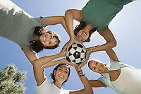 Four women holding soccer ball together view from below.