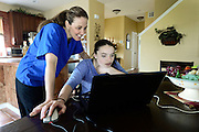 Riley Ljungdahl checks email with her mother Karen Ljungdahl, Friday, May 10, 2013, at her home in Longmont. Riley is looking for a service dog to help her with day to day activities. <br /> (Matthew Jonas/Times-Call)