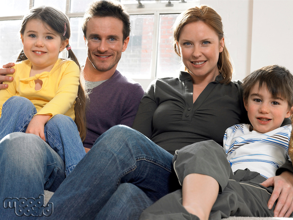 Family with two children (3-6) on couch (portrait)