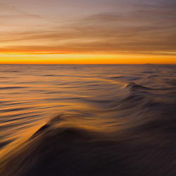 Sunset colors reflected in blurred ocean textures.