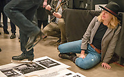 "Portland, Oregon, USA. 26 FEB, 2018. The photographer Leah Nash avoids the blades of an ice skating performance artist as he shreds  photographer Robert Frank's work at Blue Sky Gallery in Portland, Oregon, USA. The work was destroyed in a ""Destruction Dance"" performance defacing the photographs with ink and mutilation with scissors, knives and even ice skates  at the end of it's run. The destruction was Frank's protest regarding today's greed in the global art market."