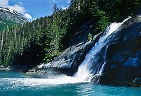 A glacier fed stream from the Coast Mountains cascades into Tracy Arm, Alaska.