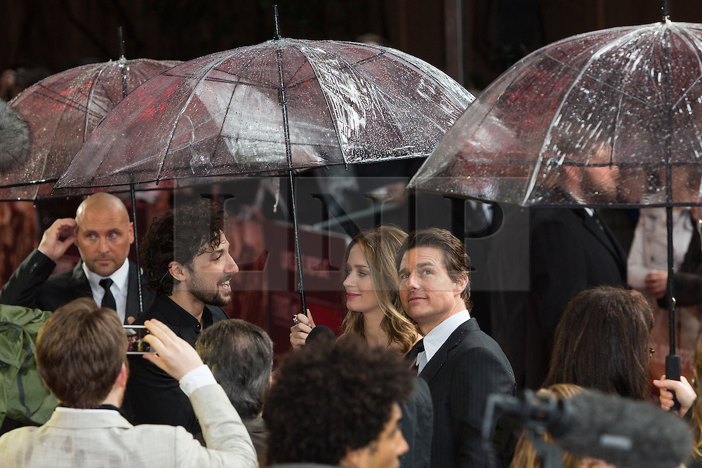 """© Licensed to London News Pictures. 28/05/2014. London, UK. Tom Cruise and Emily Blunt shelter from heavy rain under giant umbrellas this morning at the UK premiere of the """"Edge of Tomorrow"""" at the BFI IMAX in London. Photo credit : Vickie Flores/LNP"""