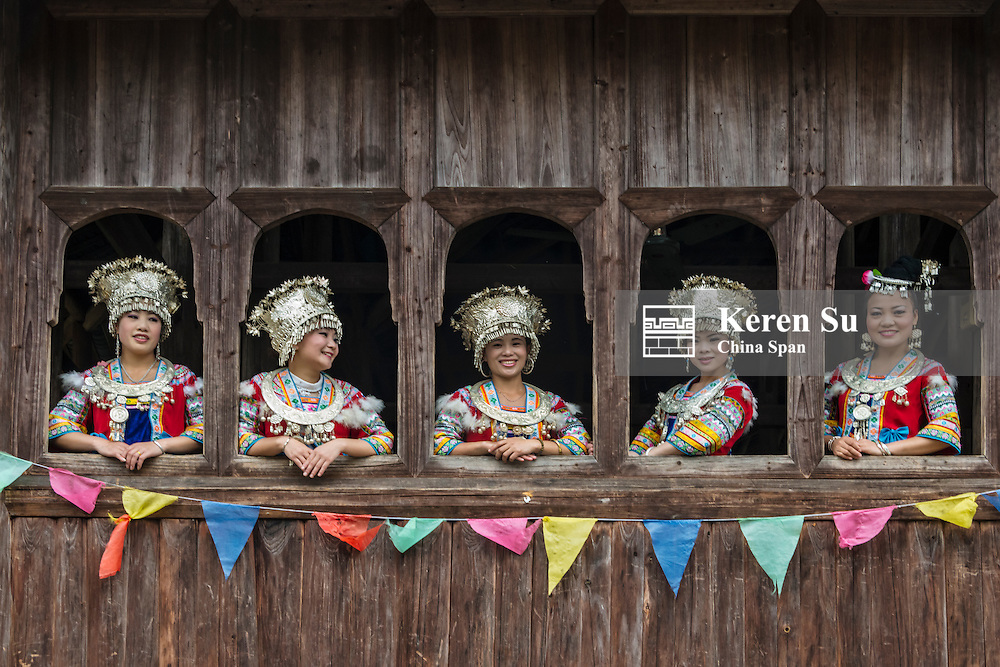 Miao girls in traditional costume by window in Miao Village, Goutan, Rongshui, Guangxi Province, China