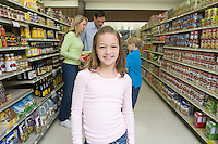 Girl stands looking at camera with family shopping in supermarket