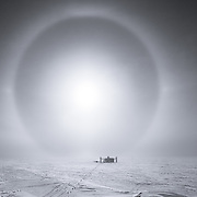 IceCube Laboratory, photographed from the roof of the Dark Sector lab, South Pole. The Lab is framed by a sun halo produced by sunlight streaming through ice crystals suspended in the air. The IceCube Laboratory is the operations center for the IceCube Neutrino Observatory.