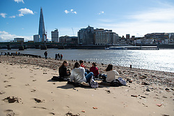 © Licensed to London News Pictures. 14/03/2019. London, UK.  Mudlarkers and sunbathers at low tide mix with workers on lunch breaks. Changeable weather sweeps up river effecting commuters and tourists, as they are hit by rain, high winds and blinding sun in the space of one hour. Photo credit: Guilhem Baker/LNP