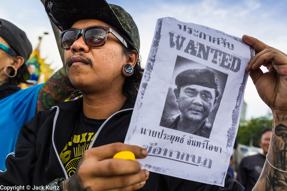 "25 MAY 2014 - BANGKOK, THAILAND:  A Thai man carries a ""wanted"" poster with a picture of Gen. Prayuth Chan-ocha, leader of the coup that unseated the elected civilian government. Public opposition to the military coup in Thailand grew Sunday with thousands of protestors gathering at locations throughout Bangkok to call for a return of civilian rule and end to the military junta.    PHOTO BY JACK KURTZ"