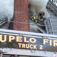 A fireman uses an outcropping of the house as a pirch to fight the fire on the second floor Monday morning.