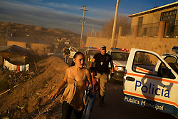 A young girl walks by a caravan of police vehicles during a security sweep looking for drug dealers, drug users and criminals.