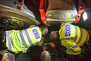 UNITED KINGDOM, London: 02 December 2015 Thousands of people gather in Parliament Square this evening as part of a Stop The War campaign. Protesters have gathered outside Parliament for a second night as they await the result of a vote on UK air strikes in Syria. <br /> Pictured: Police try and remove a protester lying under an articulated outside Parliament lorry to bring attention to the Stop The Way Campaign. Rick Findler / Story Picture Agency