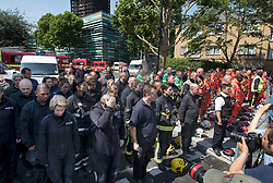 © Licensed to London News Pictures. 19/06/2017. London, UK. Members of the emergency services stand for a minutes silence for the victims of the Grenfell tower block fire. The blaze engulfed the 27-storey building killing dozens - with 34 people still in hospital, many of whom are in critical condition. Photo credit: Peter Macdiarmid/LNP