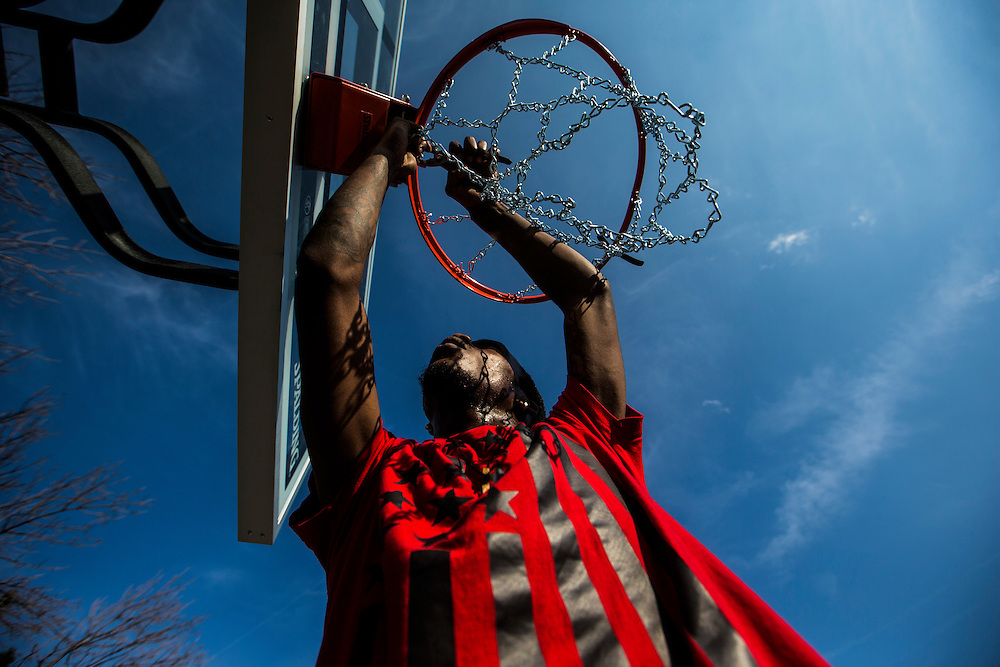 Mississauga , Ontario - August 19, 2015 -- Basketball -- Tristen Mason fixes the chain mesh on the rim at a temporary basketball court set up by the Erin Mills Youth Centre during a community event in a parking lot in Mississauga, Thursday August 19, 2015   (Mark Blinch for the Globe and Mail)
