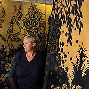 Anne Midavaine, director of the Atelier Midavaine, with lacquer and gold leaf panels with a garden design, in the workshop on the Rue des Acacias in the 17th arrondissement of Paris, France. Anne Midavaine is the granddaughter of lacquer artist Louis Midavaine, who founded the company in 1919. The workshop produces lacquer panelling, furniture and objects, mainly to commission, working with an international clientele. Picture by Manuel Cohen