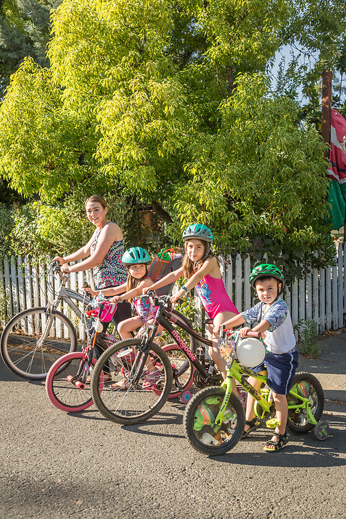 """We lived in Santa Rosa and had to get in the car to go anywhere.  Now that we live in Calistoga, we ride our bikes everywhere.""  -Special Ed Para instructor Melinda Mendoza with her kids: Nataly, Emily, and Anthony, in front of their home on Grant Street in Calistoga."
