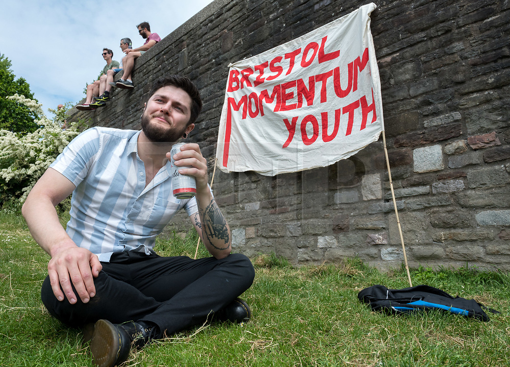 "© Licensed to London News Pictures. 25/05/2019. Bristol, UK. ISAAC (no surname given) from Bristol Momentum Youth with a can of lager at a ""drink-in"" protest, organised by Bristol Momentum Youth, held in Bristol's Castle Park against fines under a Public Space Protection Orders (PSPOs) now being implemented by Bristol City Council which are used to ban alcohol drinking in certain areas. Though most of the alcohol in public bans have been in place since late 2017, they weren't actively enforced until this year when contractor 3GS took over the council contract for litter and other rules enforcement in outside spaces from previous contractor Kingdom. The PSPO rule states that: ""No person in the restricted area shall be in possession of any opened or unsealed bottle or container of alcohol"". The fines can be up to £100 and protestors say it will disproportionately affect the least well off in the community who are also likely be targeted more with the fines in the first place, and is another step in eroding the use of public space. Photo credit: Simon Chapman/LNP."
