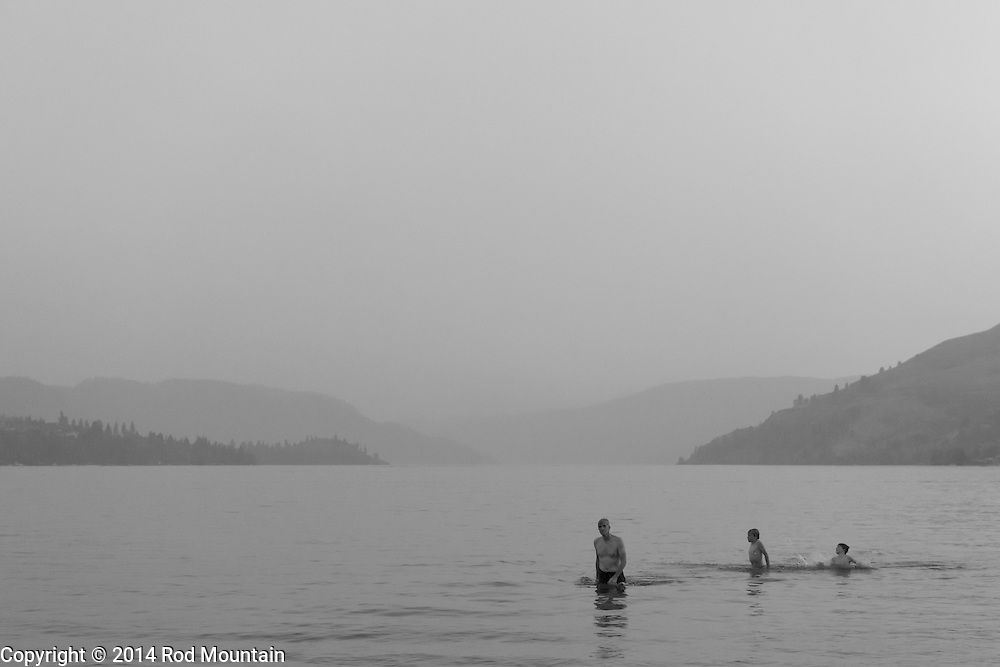 As forest fire haze fills the Okanagan valley, swimmers find  coolness at the end of a hot summer's day. Photo: © Rod Mountain