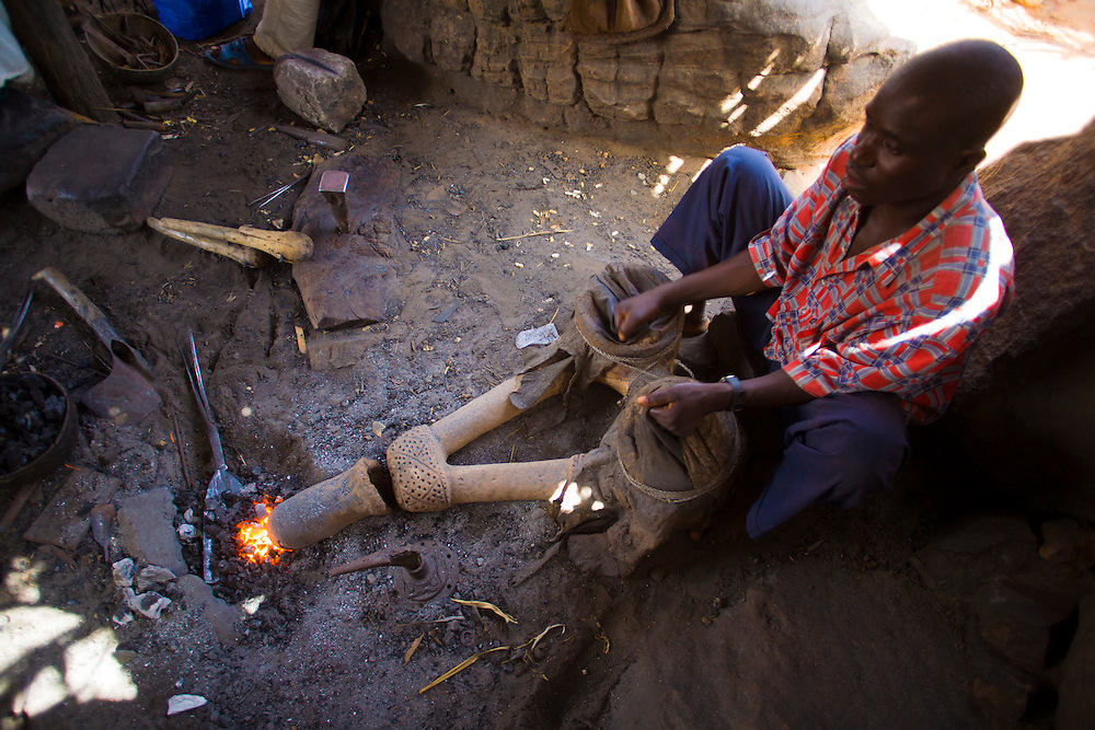 Blacksmith working with bellows to make metal statues and jewelry in Indelou village. The Dogon Country is the most visited part of Mali with tourists visiting its tipical  villages that can be located on the cliff, on the sandy plain or in the rocky plateau