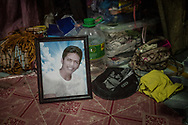 """Framed photo of the late John """"Toto"""" Dela Cruz, 16, who leaves behind a baby, Hazel and widow, Jasmin, 15.  His fanmily says they witnessed him being dragged by the hair out of this room in their makeshift house built over the waters of a swampy, contaminated estuary, onto the porch and shot in the chest and head.  Bagung Bayan, C4, Navotas, Metro Manila, Philippines."""