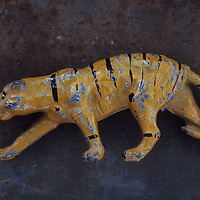 Close up of battered and scratched lead model of tiger in stalking position lying on rusty metal sheet