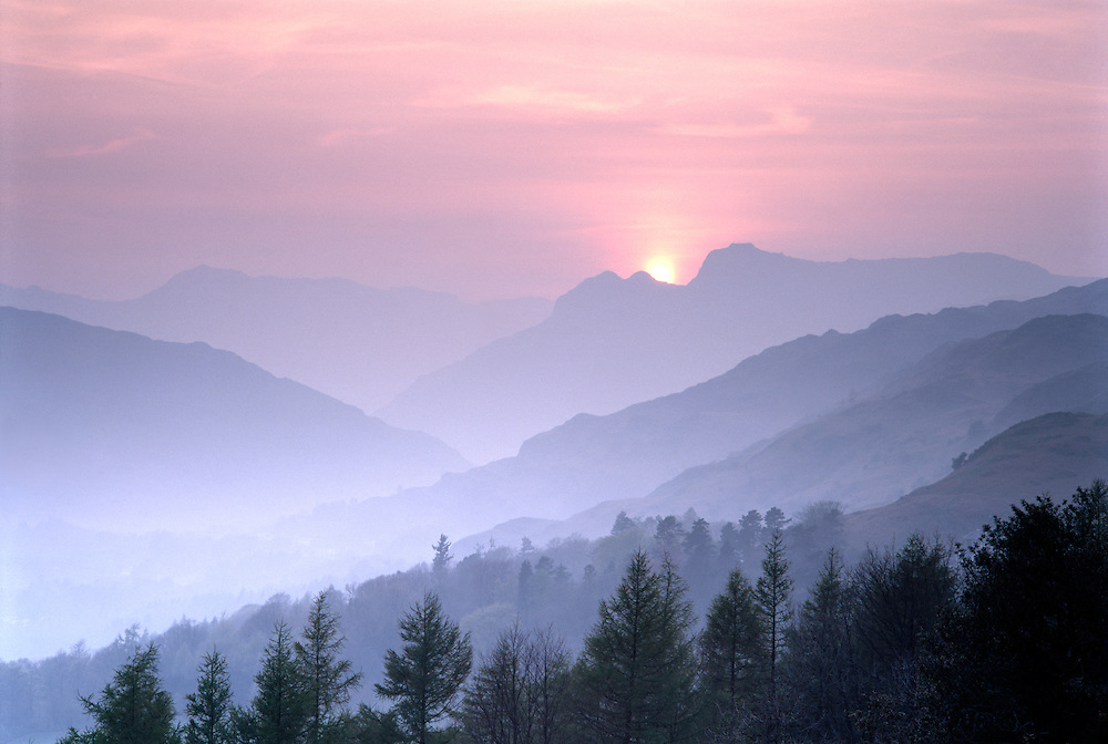 Sunset behind twin peaks of the Langdale Pikes in Langdale Valley, Lake District National Park, Cumbria, England UK
