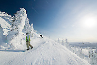 """Snowboarders just off the """"Eagle"""" chairlift ride by on the way to the backside and outback areas of Mount Washington.  Mount Washington, Comox Valley, Vancouver Island, British Columbia, Canada."""