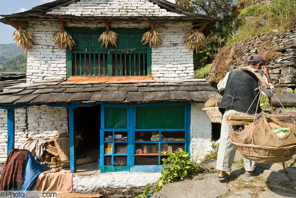 A Gurung man carries a balanced pair of loaded baskets up a stone road past a shop house drying corn, near Kimche, in the Annapurna Conservation Area, Nepal.